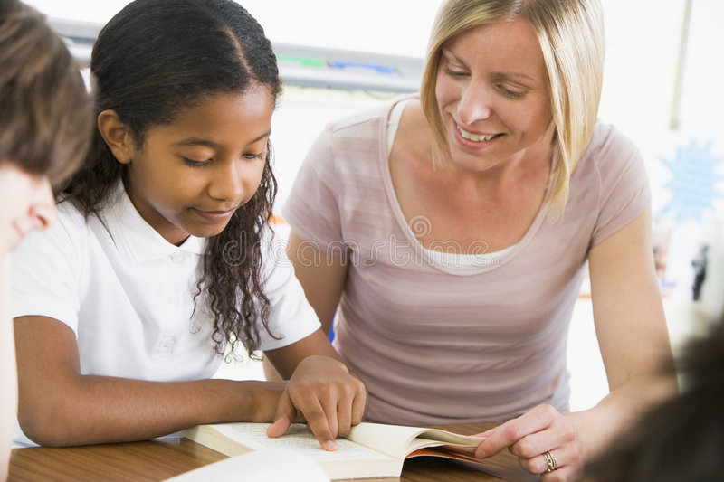 A Schoolgirl And Her Teacher Reading In Class Royalty Free Stock Images