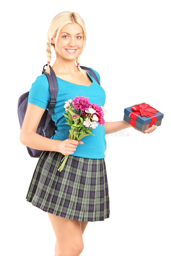 Schoolgirl holding flowers and a gift box stock photography
