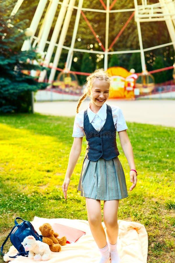 Schoolgirl joyfully dances in the park. Schoolgirl in uniform joyfully dances in the park. on the coverlet lie a backpack, books, soft toys bear stock photos