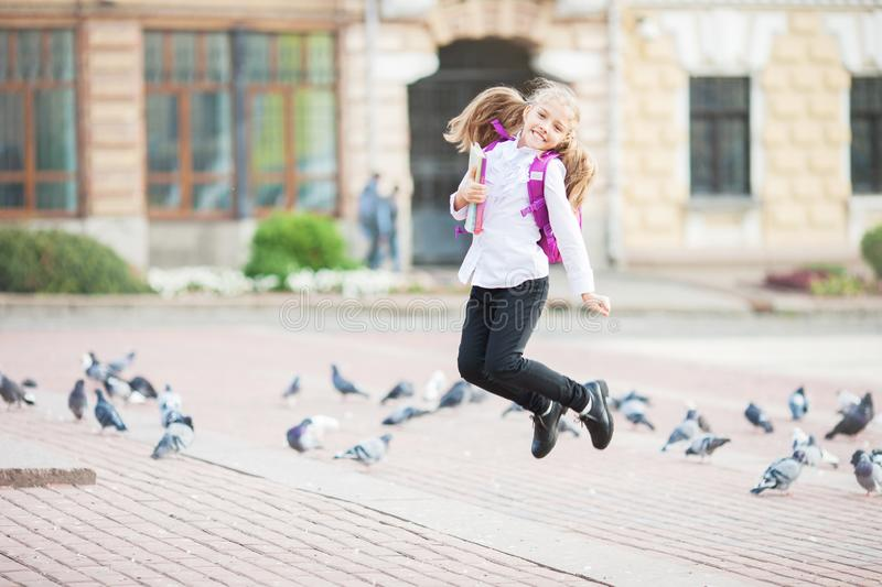 Schoolgirl jumping with a backpack and book outdoors. Education and learning concept royalty free stock photos