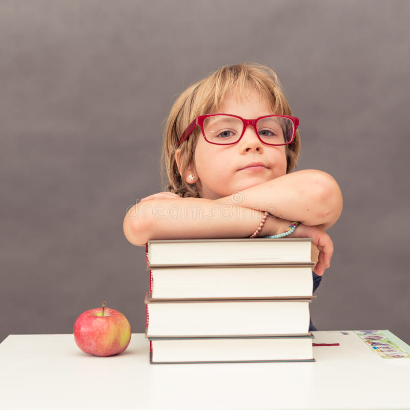 Schoolgirl leaning on a stack of books royalty free stock photography