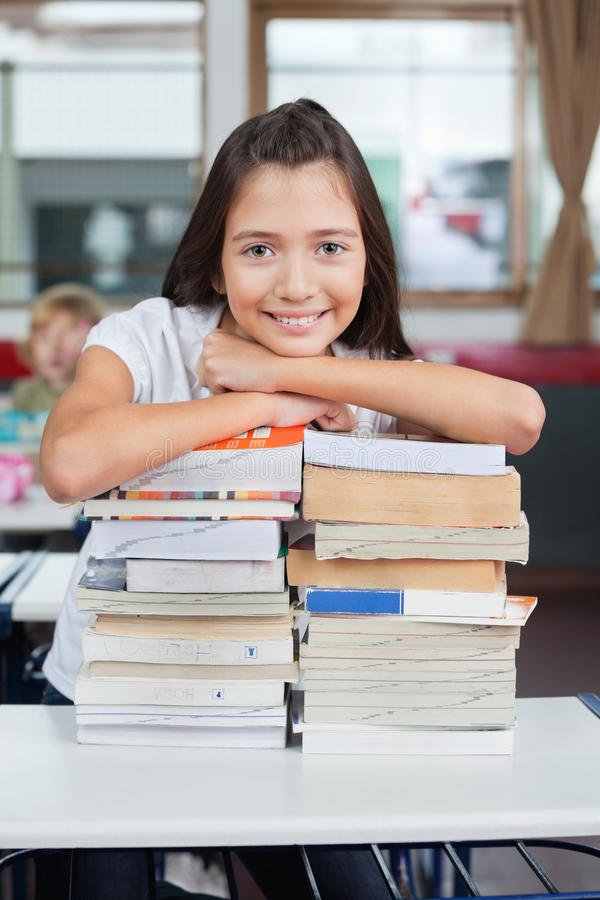 Schoolgirl Leaning On Stacked Books At Desk royalty free stock image