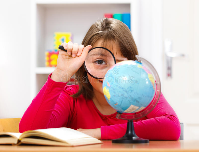 Schoolgirl with loupe. Schoolgirl playing with magnifier in geography class stock photo