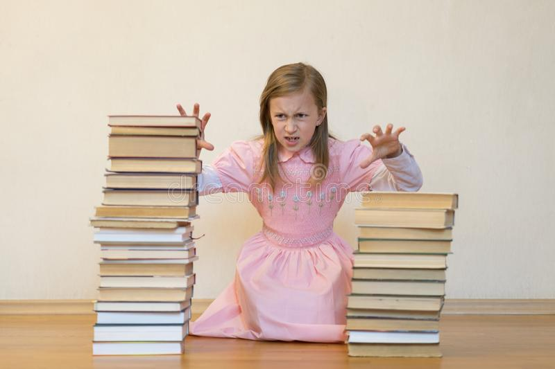 Schoolgirl is mad at books. The concept of hate to study and books. Unwillingness of a child to learn.  royalty free stock photography