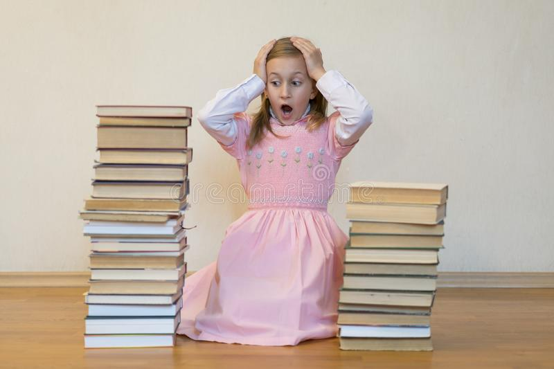 Schoolgirl is mad at books. The concept of hate to study and books. Unwillingness of a child to learn. Shock from the books. Shock. From knowledge stock image