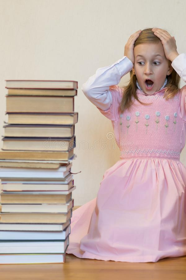 Schoolgirl is mad at books. The concept of hate to study and books. Unwillingness of a child to learn. Shock from the books. Shock. From knowledge. back to stock photo
