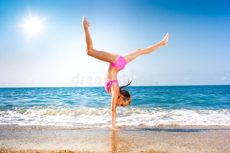 Schoolgirl making gymnastics on seashore or beach royalty free stock photos