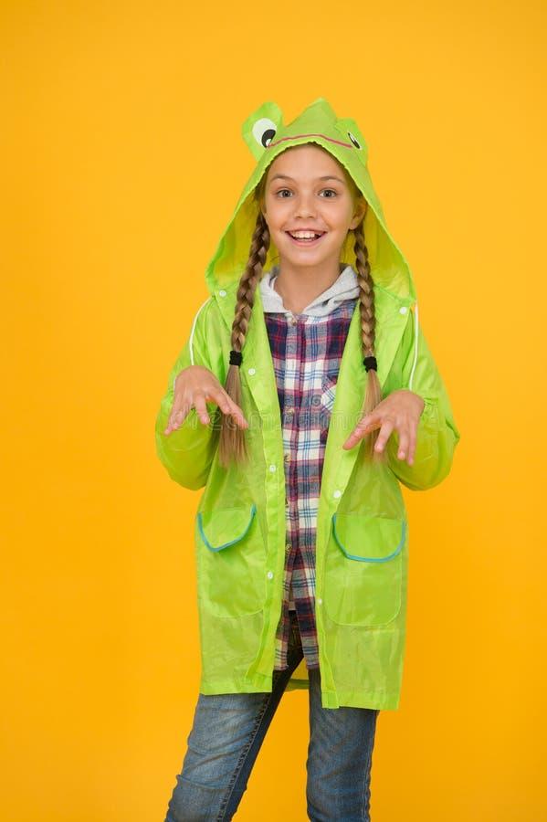 Schoolgirl met een regenjas geniet van regenachtig weer Rainproof accessoire Waterdichte kleding die elk kind moet proberen Kid g stock afbeeldingen