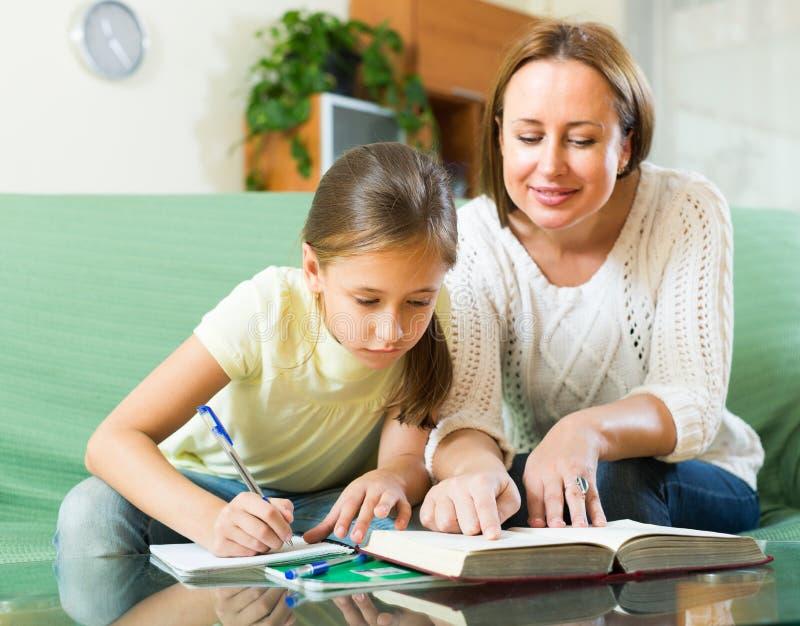 Schoolgirl and mother doing homework royalty free stock photos