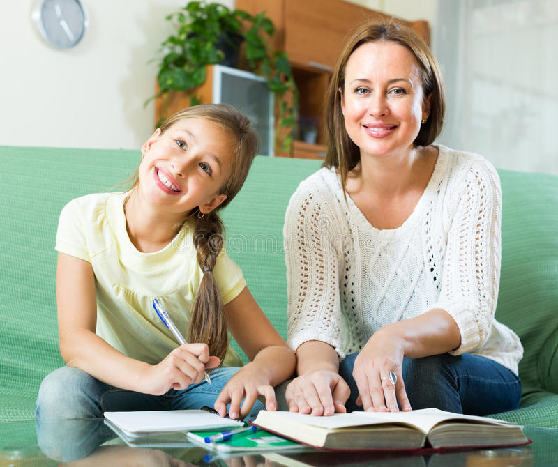 Schoolgirl and mother doing homework royalty free stock images