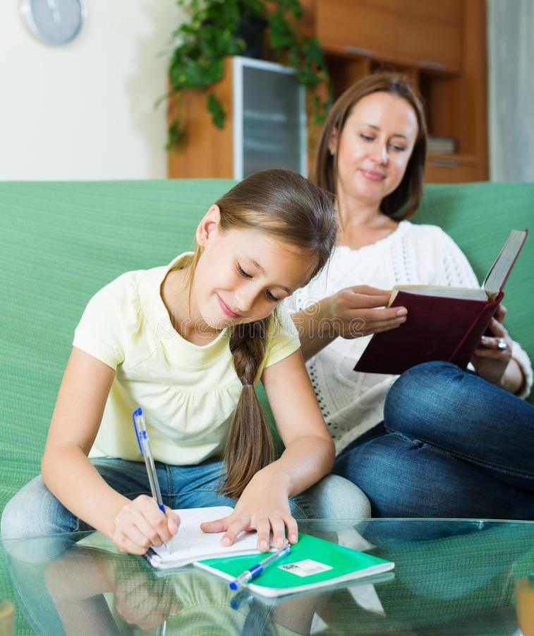 Schoolgirl and mother together doing homework stock image
