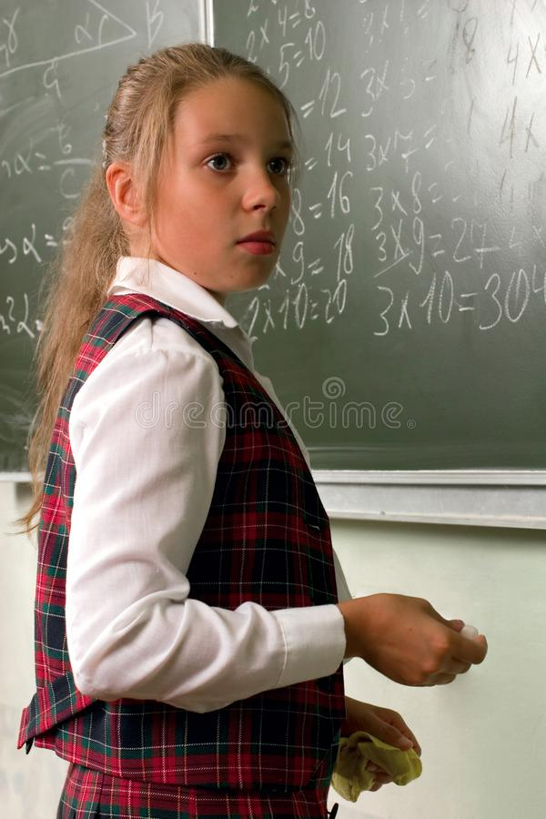 Schoolgirl på blackboarden arkivbild