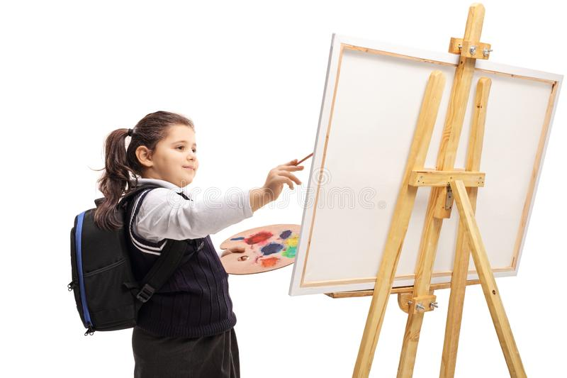 Schoolgirl painting on a canvas royalty free stock images