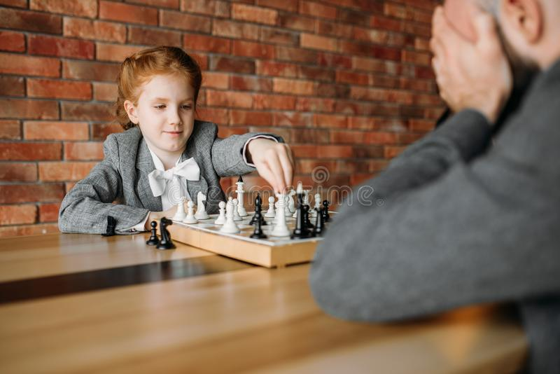 Schoolgirl playing chess with adult male person royalty free stock photo