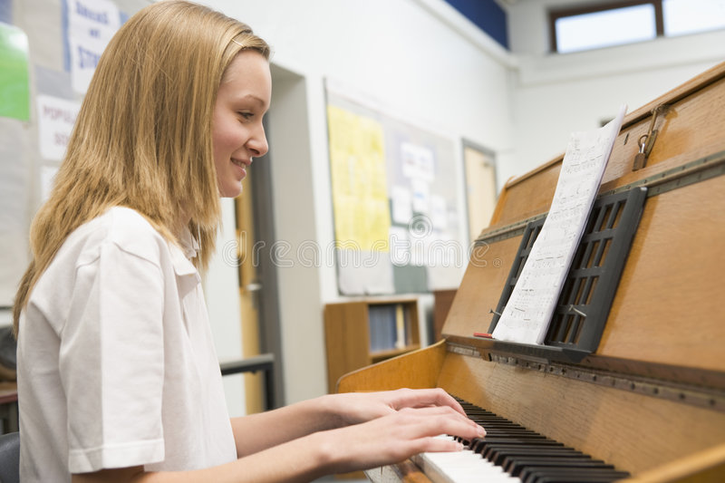 Schoolgirl playing piano in music class royalty free stock images