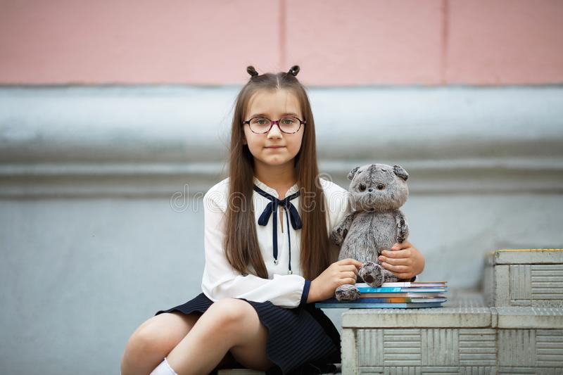 Schoolgirl with plush toy. Child girl with plush toy and textbooks sits on the steps of the school stairs. Schoolgirl portrait. Selective focus royalty free stock images
