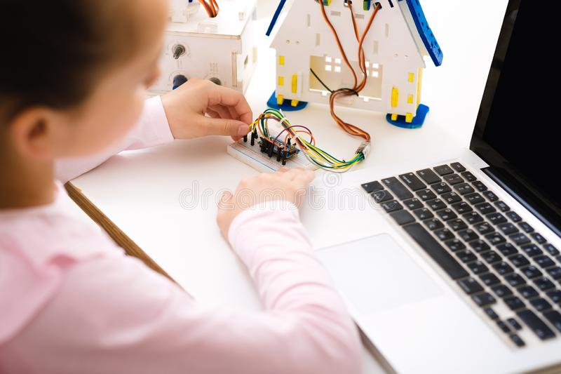 Schoolgirl programming robot with laptop computer at lesson royalty free stock images