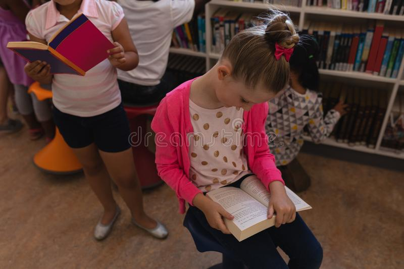 Schoolgirl reading a book and sitting on chair in school library stock photos