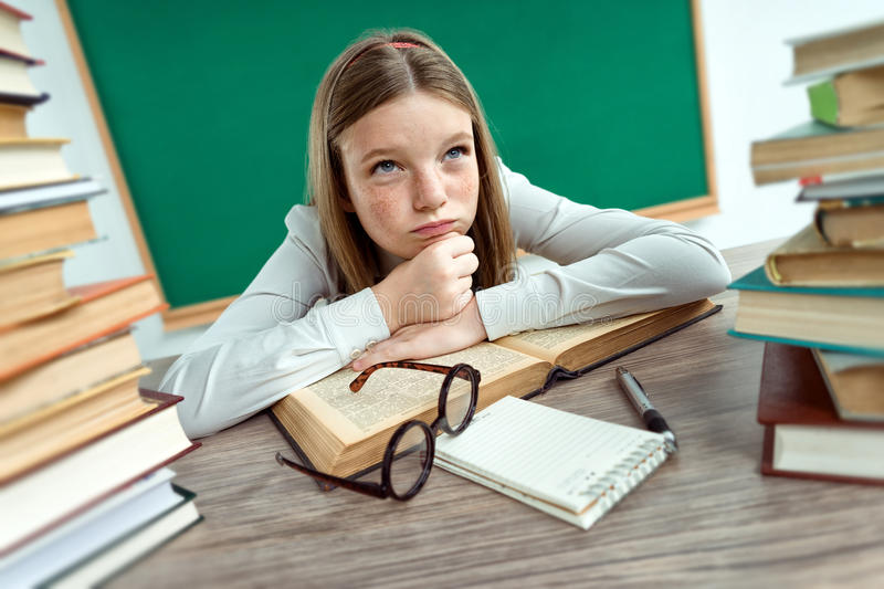 Schoolgirl resting her chin on her hands royalty free stock image