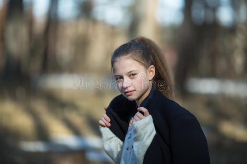 Schoolgirl`s portrait in the spring park. Happy. Schoolgirl`s portrait in the spring park royalty free stock images