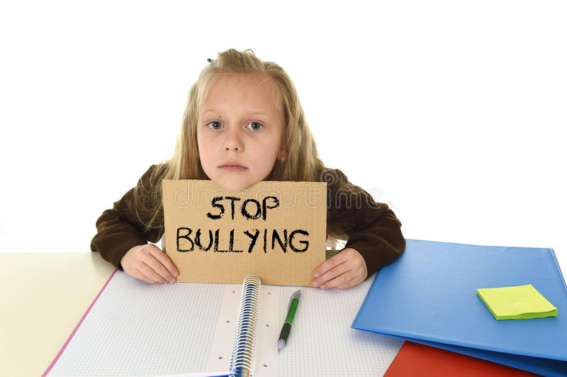 Schoolgirl scared in stress holding paper with text stop bullying desperate asking for help. Young beautiful schoolgirl scared in stress holding paper with text royalty free stock photos