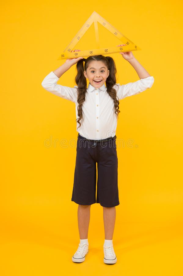 Schoolgirl school uniform hold big ruler geometry school lesson. Kid cute school student study mathematics. Triangle royalty free stock photography