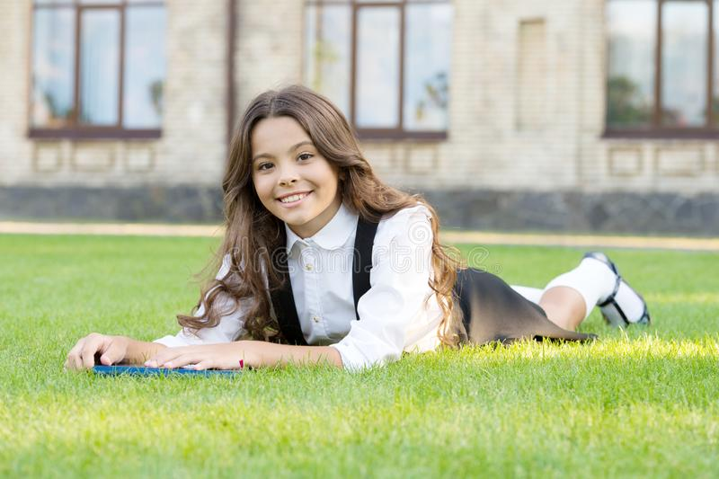 Schoolgirl school uniform laying on lawn with favorite book. Access to knowledge. Bookworm concept. Lesson on fresh air. Cute small child reading book outdoors stock photo