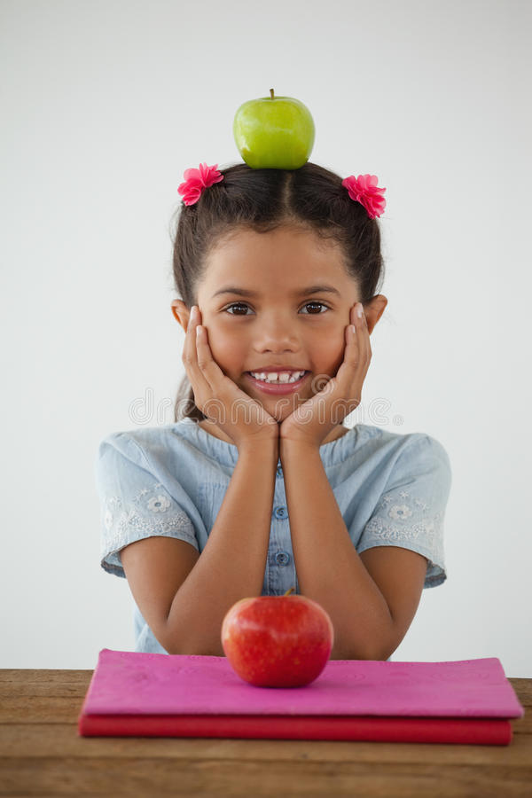 Schoolgirl sitting with green apple on her head against white background. Portrait of schoolgirl sitting with green apple on her head against white background stock image