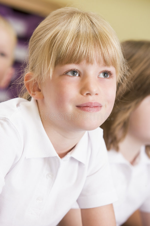 Schoolgirl sitting in primary class stock photos
