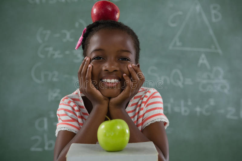 Schoolgirl sitting with red apple on her head against chalkboard royalty free stock image