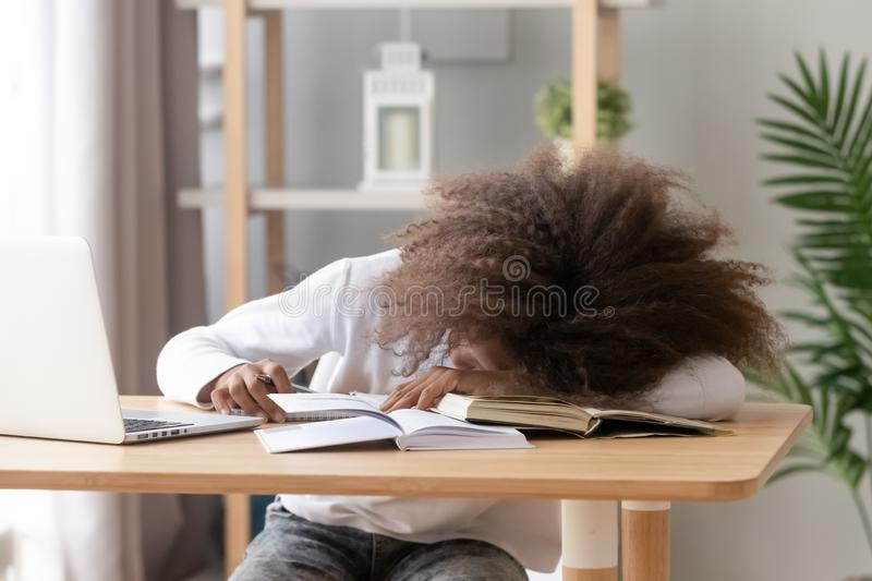 Schoolgirl sleeping sitting at desk in classroom during study royalty free stock photos