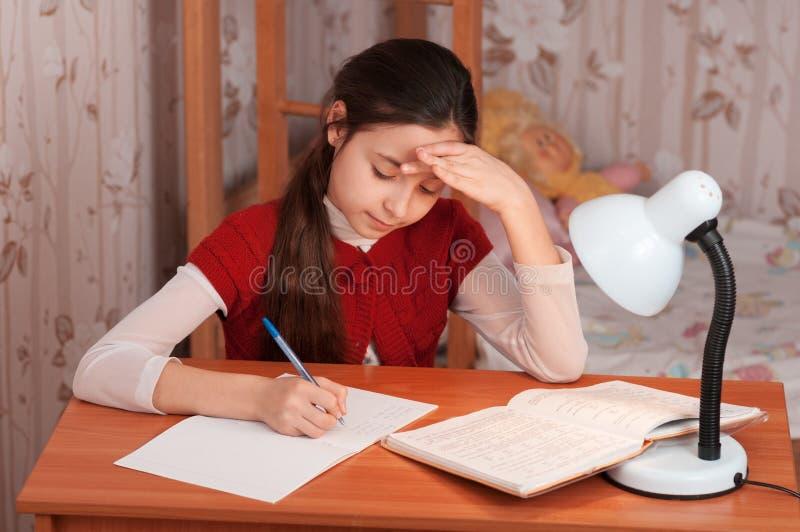 Schoolgirl som gör läxa royaltyfri bild