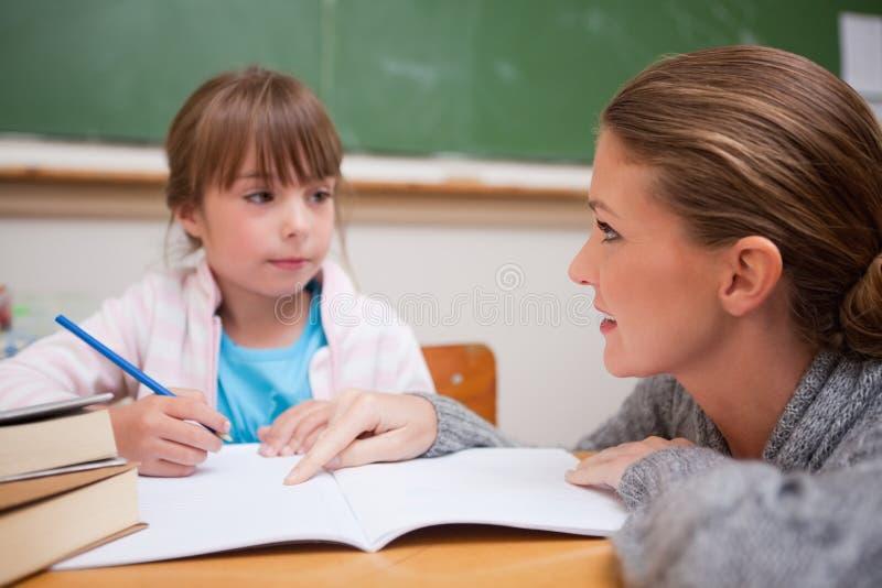 Schoolgirl som skriver en while som hon lärare talar arkivfoton