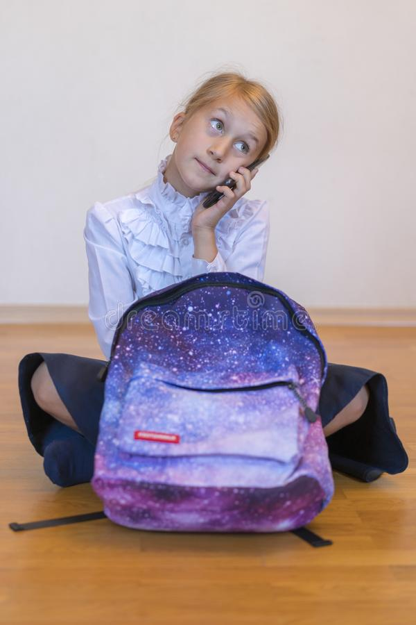 Schoolgirl speaks on a smartphone. Schoolgirl with a backpack sits on the floor and talks on the phone. vertical photo.  stock photo
