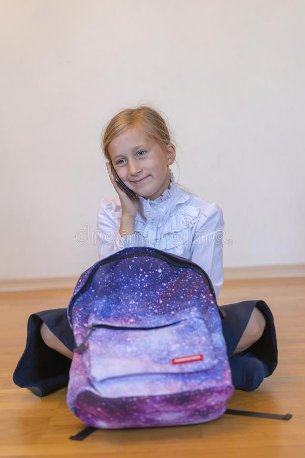 Schoolgirl speaks on a smartphone. Schoolgirl with a backpack sits on the floor and talks on the phone. vertical photo.  royalty free stock image