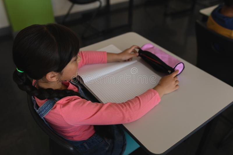 Schoolgirl studying in classroom sitting at desks in school. High angle view of schoolgirl studying in classroom sitting at desks in school royalty free stock images