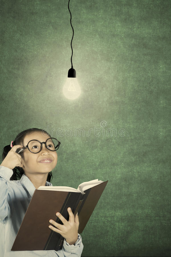Schoolgirl thinking idea with bulb. Cute schoolgirl thinking idea while looking at light bulb above her head and holding a textbook royalty free stock photography