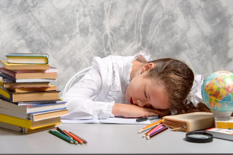 The schoolgirl tired to do homework task and fell asleep at the table. Child education concept. stock image