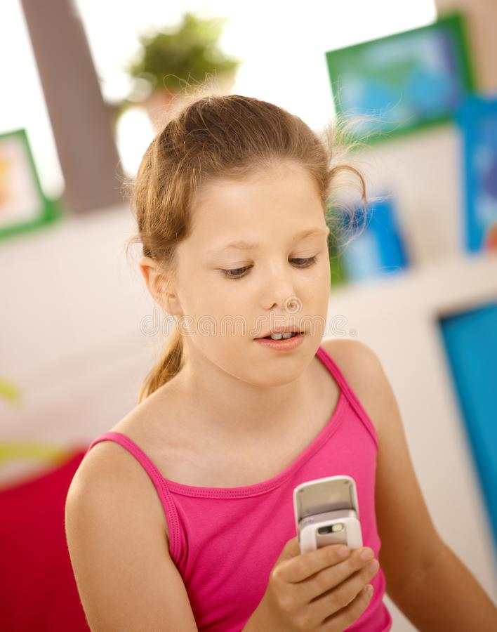 Schoolgirl using cellphone royalty free stock images
