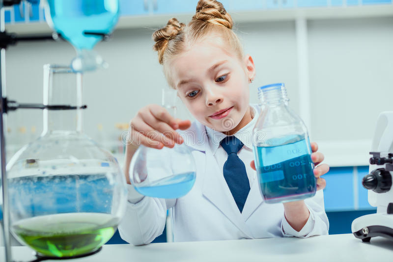 Schoolgirl in white coat making experiment with reagents stock photo