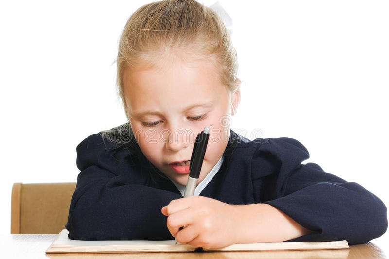 Schoolgirl writes at a table royalty free stock images