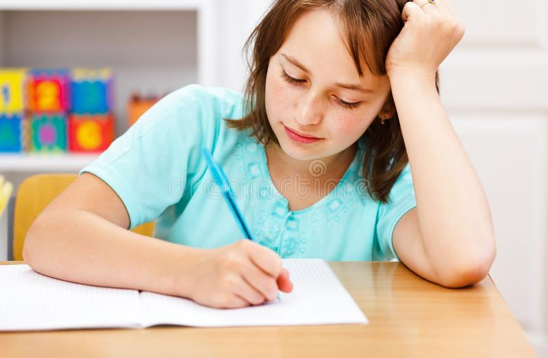 Schoolgirl writing boring homework stock photography
