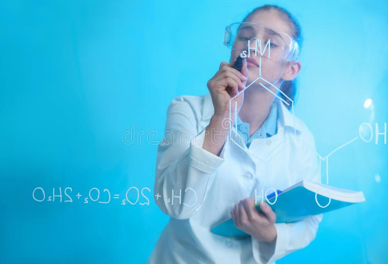 Schoolgirl writing chemistry formula on glass board against color background. Space for text royalty free stock photography