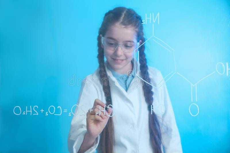 Schoolgirl writing chemistry formula on glass board. Against color background royalty free stock photography