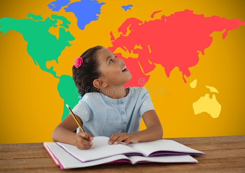 Schoolgirl writing at desk in front of colorful world map. Digital composite of Schoolgirl writing at desk in front of colorful world map royalty free stock image