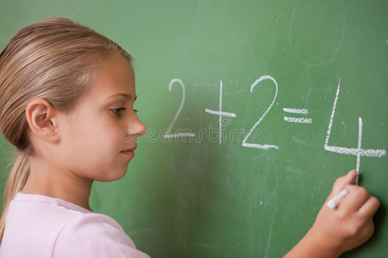 Schoolgirl Writing A Number Royalty Free Stock Image