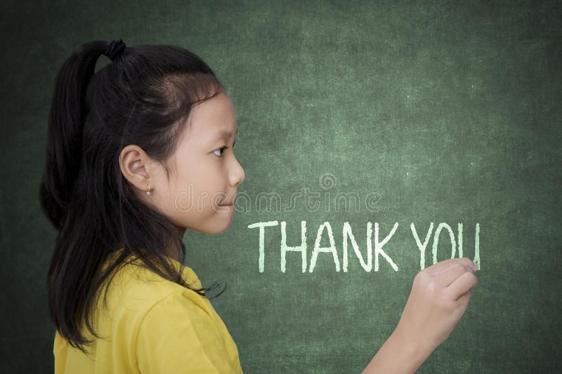 Schoolgirl writing thank you text on a chalkboard stock images