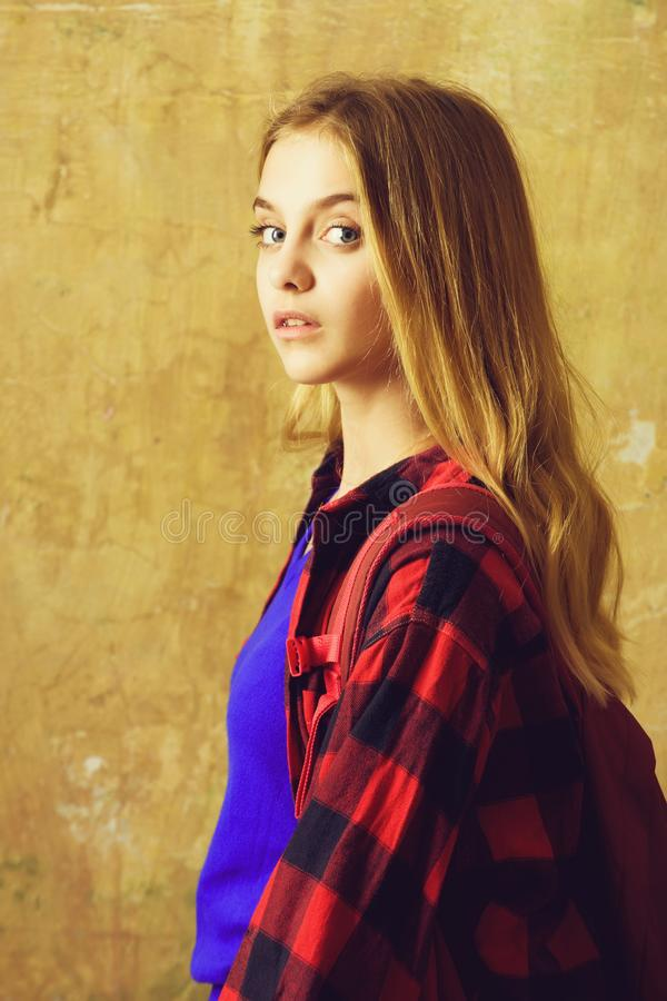 Schoolgirl or young girl in red checkered shirt with backpack stock photos