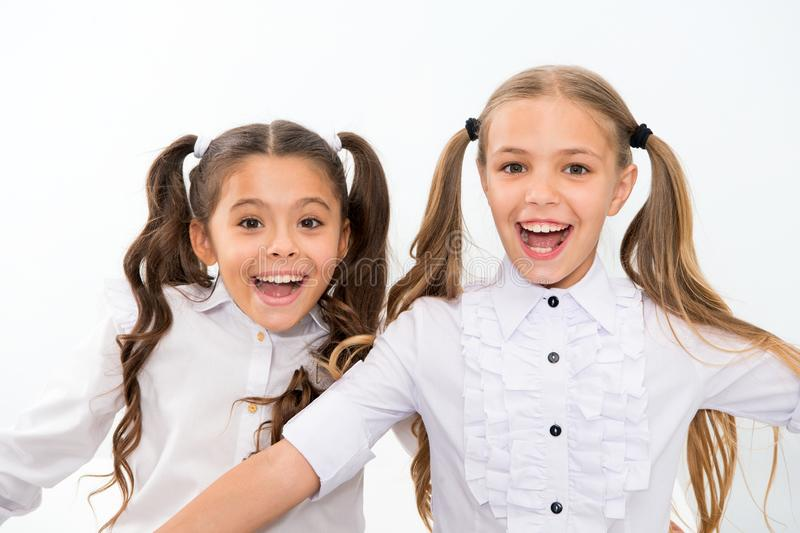 Schoolgirls with cute ponytails hairstyle and brilliant smiles. Best friends excellent pupils. Perfect schoolgirls tidy. Appearance glad to meet you. Meet new royalty free stock photography