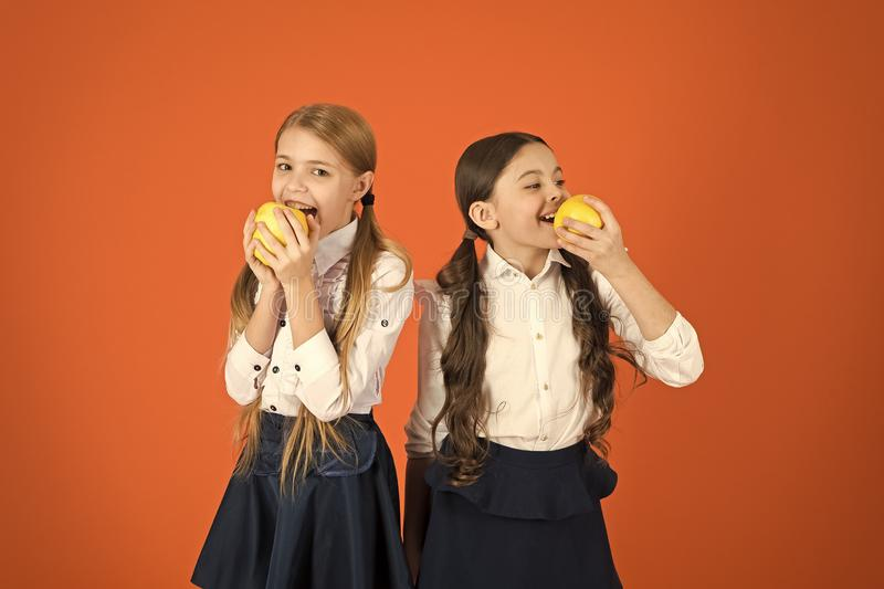 Schoolgirls eat apples. School lunch. Vitamin nutrition during school day. Boost student acceptance of fruit. Distributing free fresh fruit at school. Girls stock images